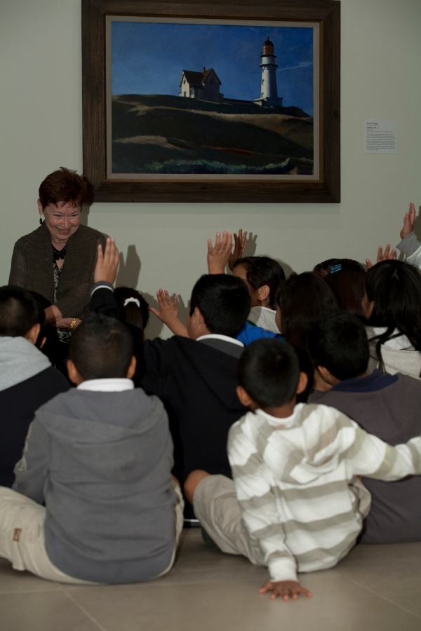 Marilyn, a DMA Docent, talks with students about Edward Hopper's Lighthouse Hill.