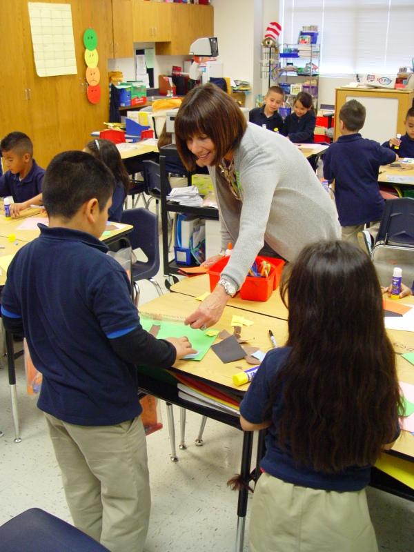 Karen, a Go van Gogh volunteer, helps students with an art project