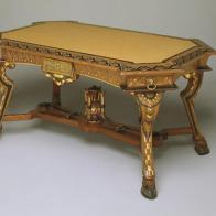 Move over plywood desks and tables! This Egyptian revival style library table is so beautiful that the kids will be begging to do their homework. The ox-hoof feet, bronze plaques, and winglike decoration all derive from ancient sources and indicate the influence of Egyptian motifs in decorative furnishings during the nineteenth century. This table is also innovatively designed, with its unusual placement of drawers that pull out diagonally from each corner. The table top was covered in fabric as well, to minimize damage to books.