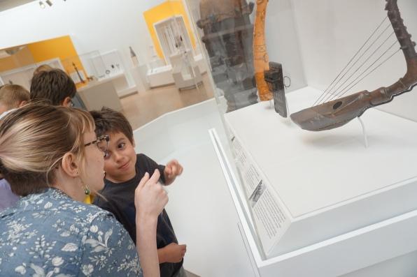 Kristin and a camper investigate art in the African Galleries.
