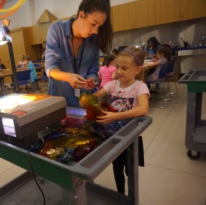 Madeline helps a camper sort through materials for a colorful project.