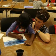 Jenna and a camper work together on a project.