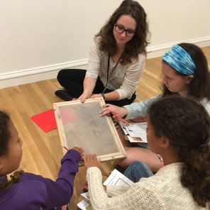 Paige shares a silkscreen used in printmaking with campers in the gallery.